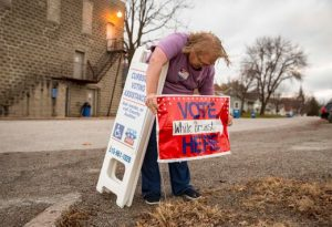 A poll worker sets up 'vote here' signs outside of a polling place, including a curbside voting sign